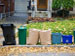 assorted trash and recycling containers at curb