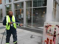 photo of DPW employee removing graffiti from a public surface